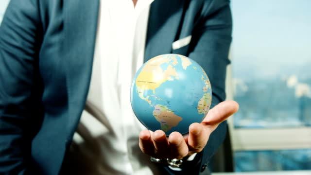 businessman holding globe - leadership stock videos & royalty-free footage