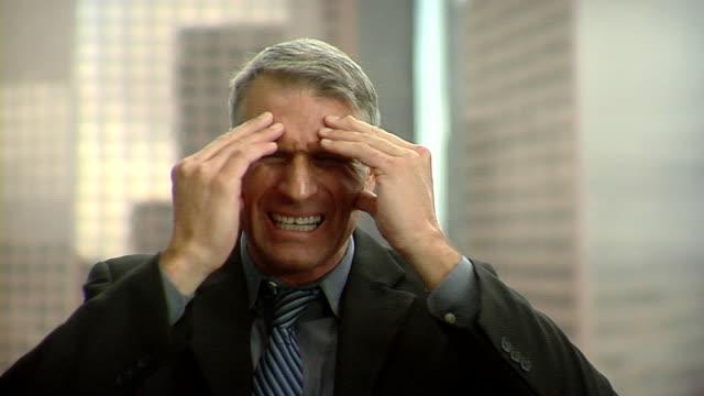 cu businessman holding head in hands making face, los angeles, california, usa - hel kostym bildbanksvideor och videomaterial från bakom kulisserna