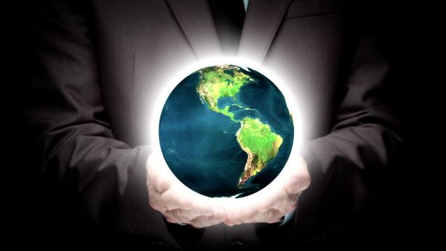 businessman holding illuminated globe - leadership stock videos & royalty-free footage