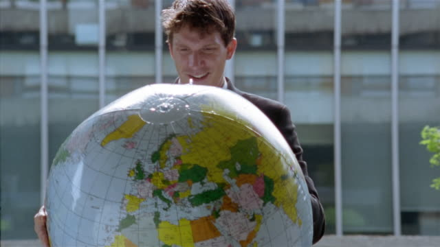 businessman holding inflatable globe outside office building / throwing and catching globe / london, england - inflatable stock videos & royalty-free footage