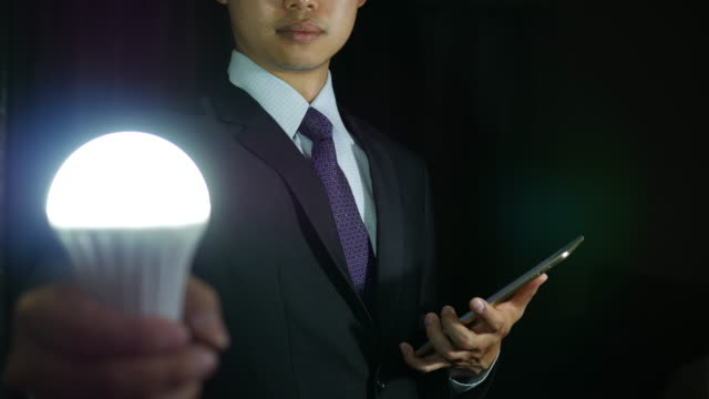 Businessman Holding Light Bulb and tablet