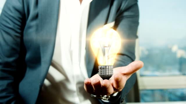 Businessman Holding Light Bulb | Idea
