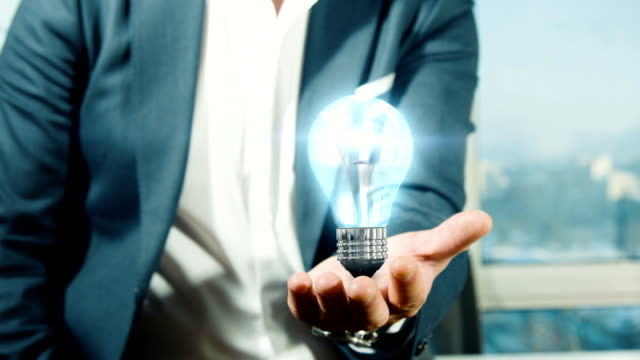 stockvideo's en b-roll-footage met businessman holding light bulb | idea - ideas