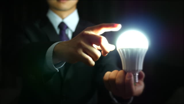 Businessman holding lightbulb