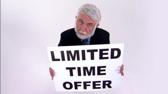 businessman holding limited time offer sign - only mature men stock videos & royalty-free footage