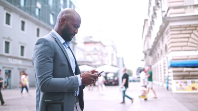 businessman holding mobile phone and standing on city street - dolly shot stock videos & royalty-free footage