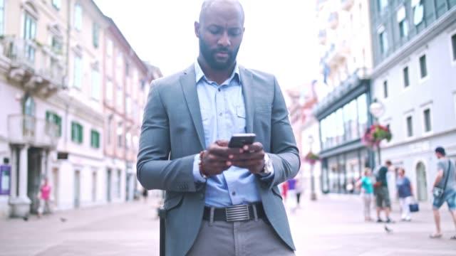 vídeos de stock, filmes e b-roll de empresário, segurando o telefone móvel e parado na rua da cidade - origem africana