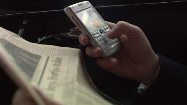 cu, businessman holding newspaper and texting on blackberry pda smart phone on car back seat, close-up of hands, singapore - 2007 stock-videos und b-roll-filmmaterial