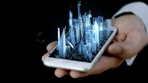 vídeos y material grabado en eventos de stock de empresario sosteniendo teléfono con holograma 3d transparente azul de la ciudad - holograma
