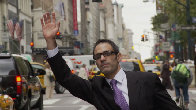 CU ZO Businessman holding smart phone and hailing cab on busy street / New York City, New York, USA