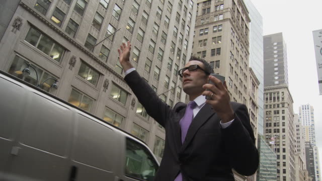 MS LA Businessman holding smart phone and hailing cab on street / New York City, New York, USA