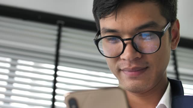 スマートフォンを持ち、オフィスを見ているビジネスマン - 出張点の映像素材/bロール