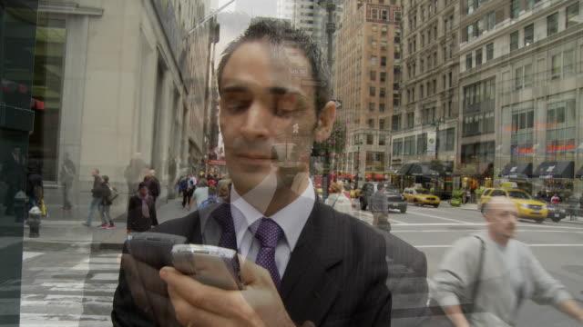 T/L CU Businessman holding smart phone on busy street / New York City, New York, USA
