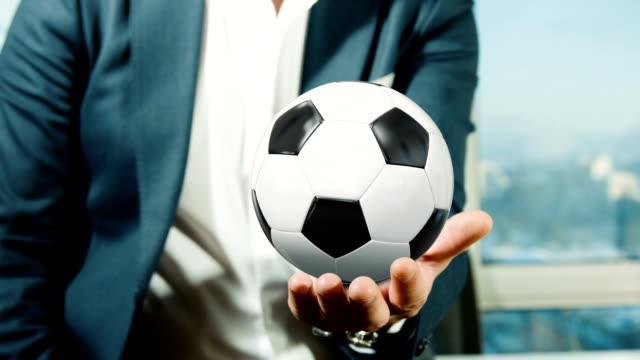 geschäftsmann hält fußball-spielball - halten stock-videos und b-roll-filmmaterial