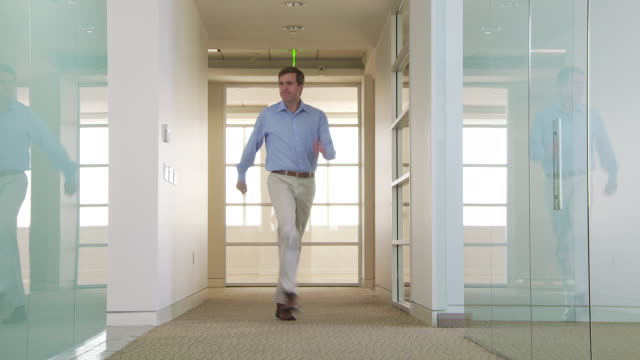 Businessman humorously walking down office hallway
