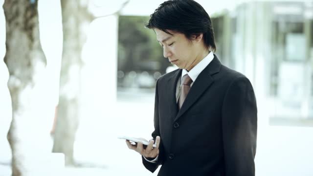 businessman idly checking phone - ビジネスマン点の映像素材/bロール