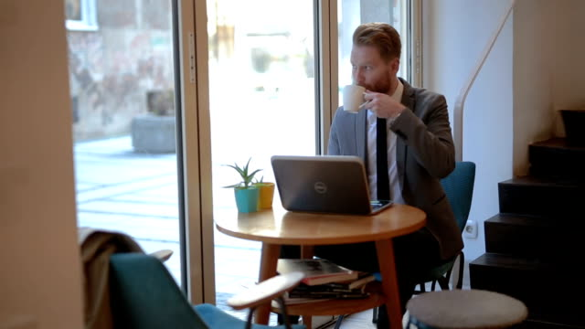 Businessman in a cafe using laptop and relaxing with favorite tea