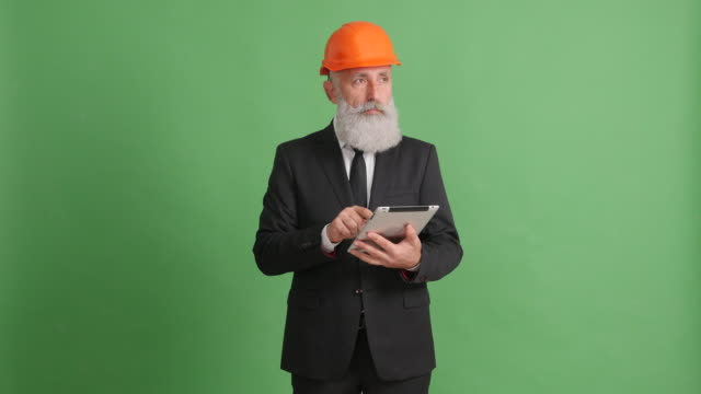 businessman in a helmet and with a tablet on a green background - 50 59 years video stock e b–roll