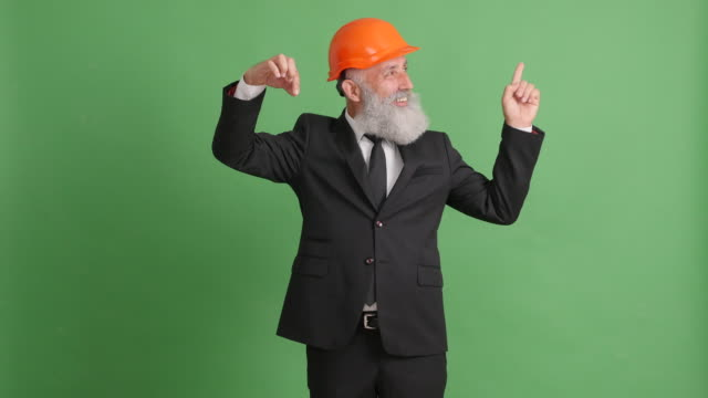 businessman in a helmet and with something in his hand on a green screen - 50 59 years video stock e b–roll
