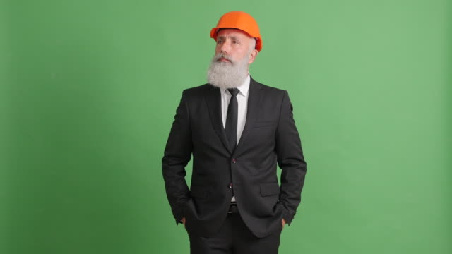 businessman in a helmet looks around and examines something on the green screen - solid stock videos & royalty-free footage