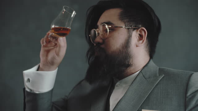 businessman in a suit drinking whiskey or cognac on black background - unhealthy living stock videos & royalty-free footage