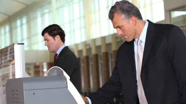 Businessman in airport/ picking up ticket at airport kiosk
