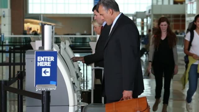 businessman in airport/ picking up ticket at airport kiosk - flugpassagier stock-videos und b-roll-filmmaterial