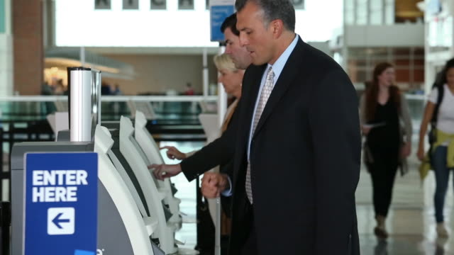 vídeos de stock, filmes e b-roll de businessman in airport/ picking up ticket at airport kiosk - ticket