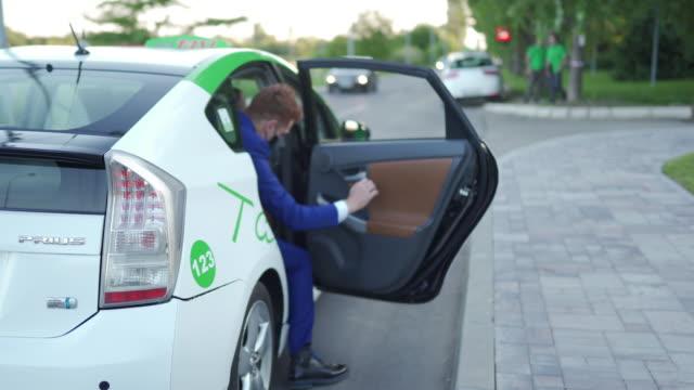 タクシーに入る青いスーツを着たビジネスマン - タクシー点の映像素材/bロール