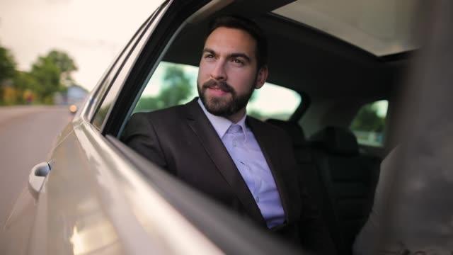 vidéos et rushes de homme d'affaires dans la voiture regardant par la fenêtre - dedans
