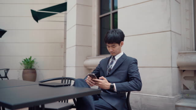 a businessman in casual clothing using smartphone for his work - freelance work stock videos & royalty-free footage