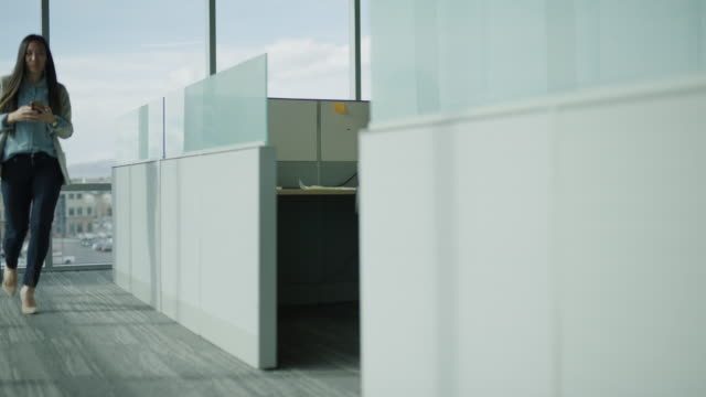 businessman in cubicle staring at businesswoman passing in office / pleasant grove, utah, united states - 性的嫌がらせ点の映像素材/bロール
