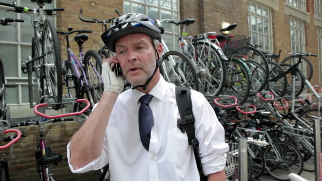 vidéos et rushes de businessman in cycle helmet, talking on cellphone - casque de vélo