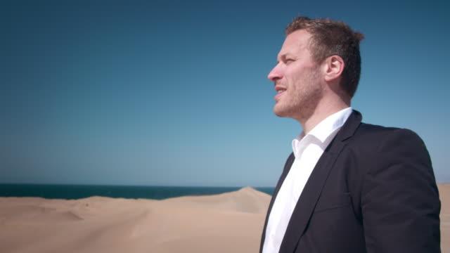 vídeos de stock, filmes e b-roll de empresário no deserto - dia