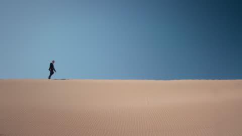 vidéos et rushes de homme d'affaires dans le désert - ligne d'horizon au dessus de la terre