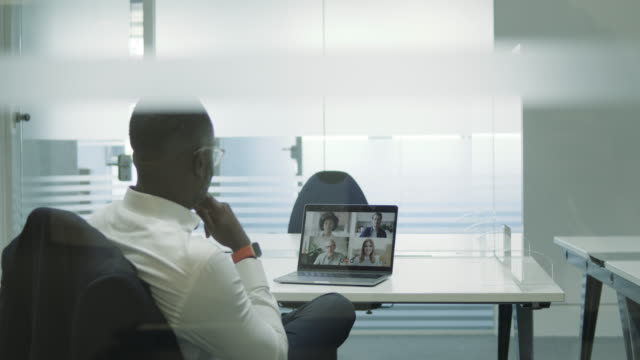 businessman in empty meeting room using video conferencing technology - corporate business stock videos & royalty-free footage