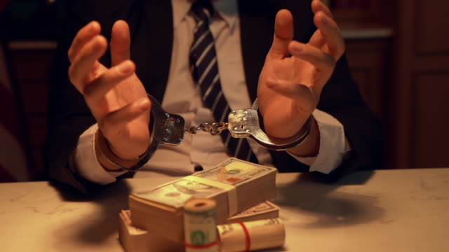 stockvideo's en b-roll-footage met zakenman in handboeien houdt geld gearresteerd. zakenman in functie in handboeien die een omkoping van eurobankbiljetten bezitten. gearresteerd terrorist. financiële criminaliteit, dirty money en corruptie concept. selectieve focus. - omkoping