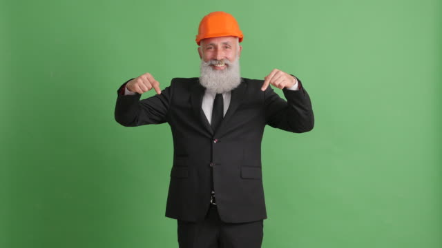 businessman in hard hat shows copy space on green screen - 50 59 years video stock e b–roll