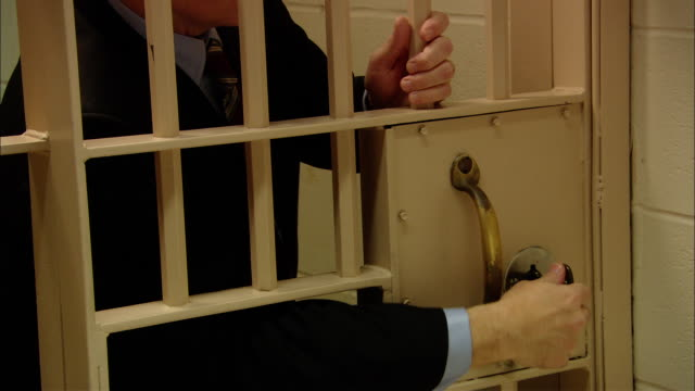 ms businessman in jail cell gripping bars/ man noticing key in lock, turning key, opening door, and escaping/ new jersey - prison escape stock videos and b-roll footage