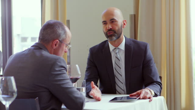 ms businessman in meeting with client in restaurant presenting document on digital tablet. - riunione commerciale video stock e b–roll
