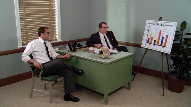 ws businessman in office for meeting with boss/ men talking and pointing to sales graph/ new york city - hel kostym bildbanksvideor och videomaterial från bakom kulisserna