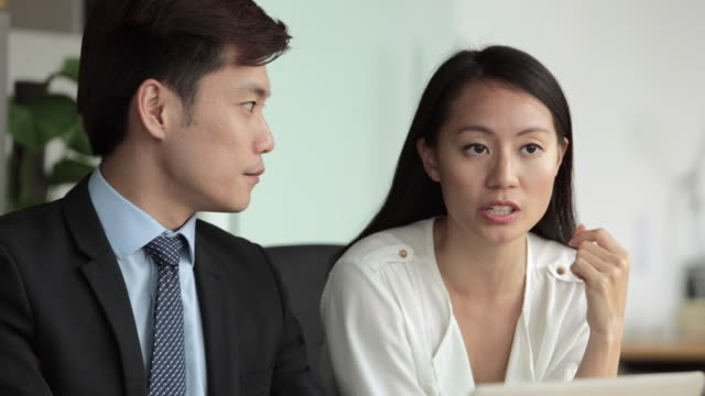 vídeos de stock, filmes e b-roll de ms selective focus pan businessman in suit and female colleague speaking to male person across desk / singapore - traje completo