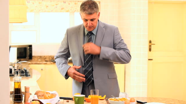 Businessman in suit hurriedly taking his breakfast / Cape Town, Western Cape, South Africa