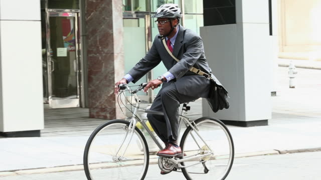 ws ts businessman in suit riding bicycle to work in city / richmond, virginia, usa - cycling helmet stock videos & royalty-free footage