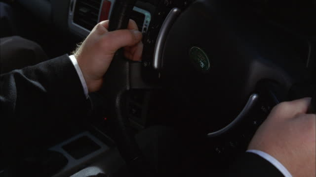 SHAKY Businessman in suit steering car with dark interior