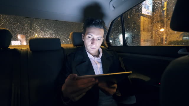 Businessman in the car using a digital tablet.
