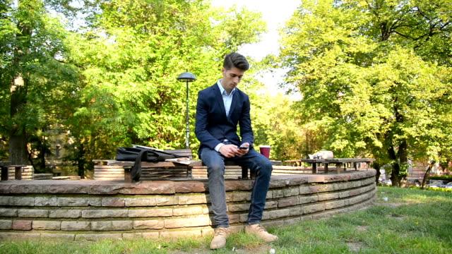 vídeos de stock, filmes e b-roll de um homem de negócios no parque - smart