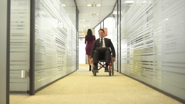 hd dolly: businessman in wheelchair coming to work - disability stock videos and b-roll footage