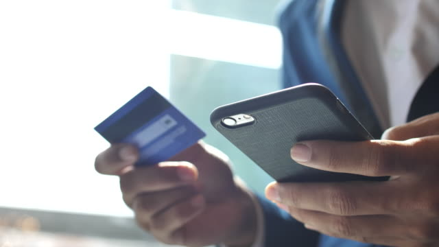 businessman inserting credit card number on mobile phone, slow motion - acquisto con carta di credito video stock e b–roll