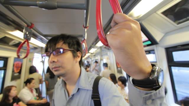uomo d'affari tiene la cintura in treno - imbracatura di sicurezza video stock e b–roll